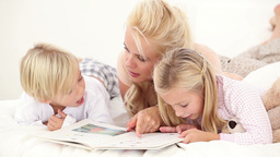 Mother reading book to her children Stock Video Footage