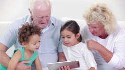 Two grandparents and two children using a tablet Footage