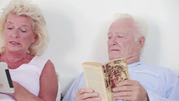 Old couple using a tablet and book Stock Video Footage