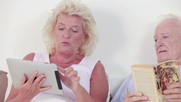 Old couple using a tablet and book Footage