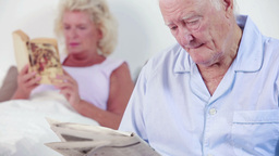 Old couple reading a book and newspaper Footage
