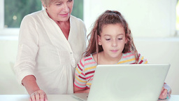 Child learning to use laptop with grandmother Footage