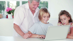 Child learning to use laptop with grandfather Footage