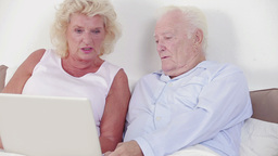 Old couple using a laptop and speaking Footage