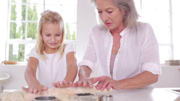 Grandmother and granddaughter using a rolling pin Stock Video Footage
