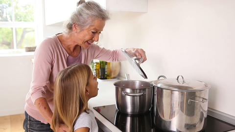 Girl happily cooking with her grandmother Footage