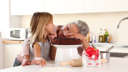 Granny putting icing on granddaughters nose Footage