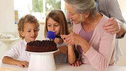 Grandmother icing cake with grandchildren Stock Video Footage
