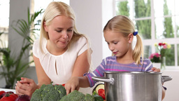 Mother and daughter putting vegetables in a pan Footage
