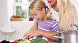 Focused mother teaching cutting vegetables Footage