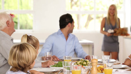 Family watching as mother brings turkey to table Footage