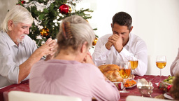 Family Saying Grace At The Dinner Table stock footage