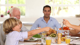 Mother serving up carrots for son at family dinner Stock Video Footage