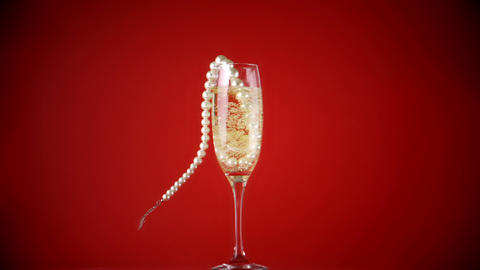 String of pearls falling into champagne flute Stock Video Footage