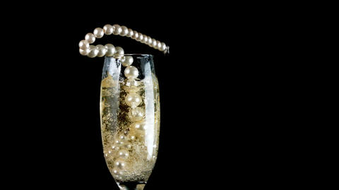 Pearl necklace falling into champagne Footage
