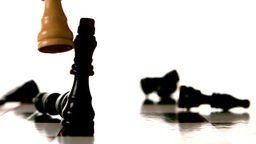 White chess piece knocking over many black pieces Live Action