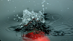 Red pepper falling into water Footage
