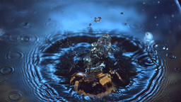 Wooden ring falling into blue water Stock Video Footage