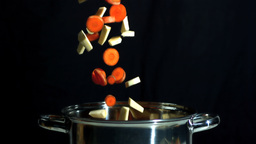 Sliced carrot and parsnip falling into saucepan on Footage