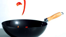 Sliced red peppers falling into wok Footage