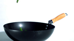Sliced green pepper falling into wok Footage