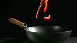 Sliced red pepper falling into wok on black backgr Stock Video Footage