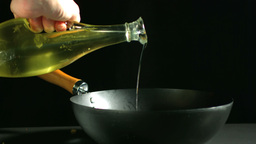 Olive oil being poured into wok Footage