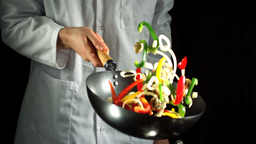 Chef tossing vegetable stir fry in wok ビデオ