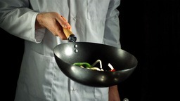 Chef tossing vegetable stir fry in wok Stock Video Footage