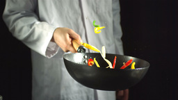 Chef tossing vegetable stir fry in a wok ビデオ