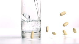 Pills falling and glass of water being filled Footage