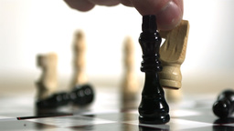 Hand using white knight to knock over king in chess Footage