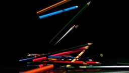 Colouring pencils falling on black background Footage