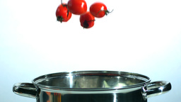 Cherry tomatoes falling in pot Stock Video Footage