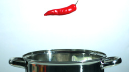Red thai chili falling in a pot Live Action
