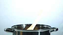 Wooden spoon falling in a saucepan Footage