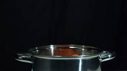 Carrots falling in saucepan on black background Footage
