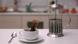 Sugar cube falling into coffee cup in kitchen Footage
