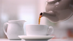 Teapot pouring tea into cup Footage