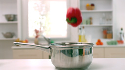 Red pepper falling in saucepan in kitchen Stock Video Footage