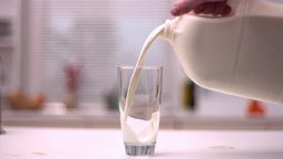Milk Being Poured Into Glass In Kitchen stock footage