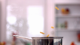 Fusilli falling into saucepan in kitchen Footage