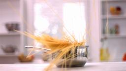 Spaghetti falling in a saucepan in kitchen Footage