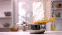 Spaghetti falling in pot in kitchen Stock Video Footage