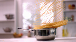 Spaghetti falling in pot in kitchen Footage