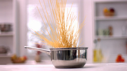Spaghetti falling in a pot in kitchen Footage