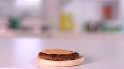 Slice of cheese falling on bun burger in the kitch Stock Video Footage