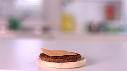 Slice of cheese falling on bun burger in the kitchen Footage