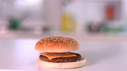 Bun falling on cheese burger in kitchen Footage
