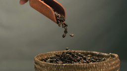 Hand pouring coffee beans from a wooden spoon into Footage